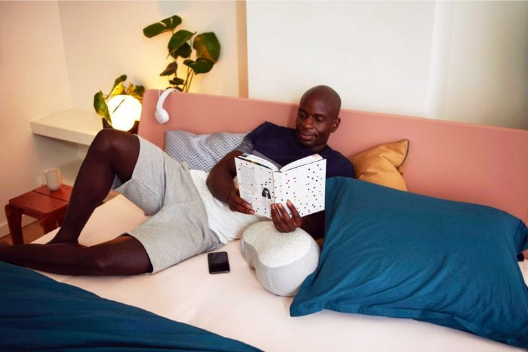 Man reading in bed; bamboo nightstands