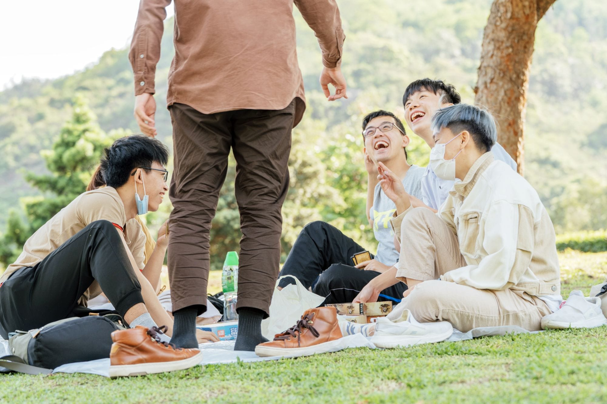 Friends at a picnic laughing; bamboo cutlery