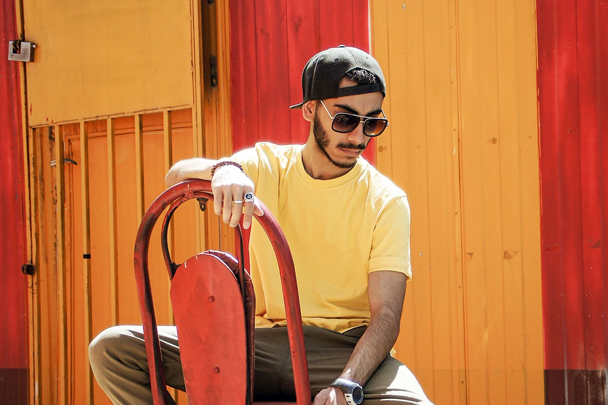 Man sitting on chair outside wearing bamboo sunglasses