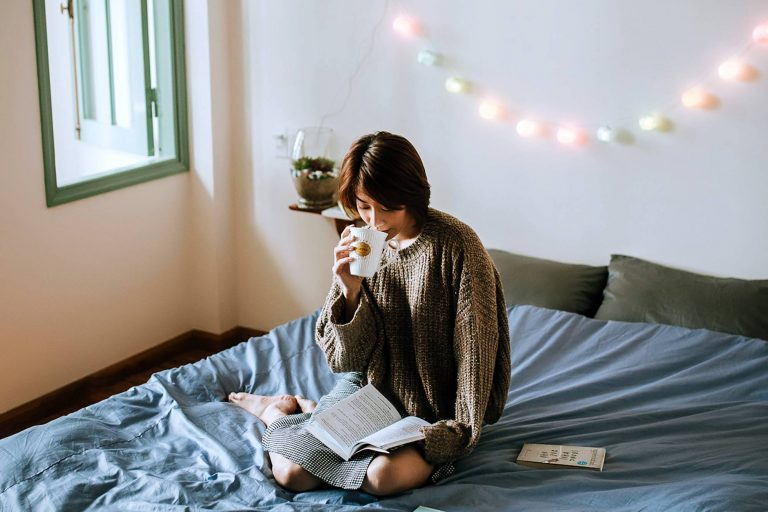 Woman in bed reading; bamboo comforters