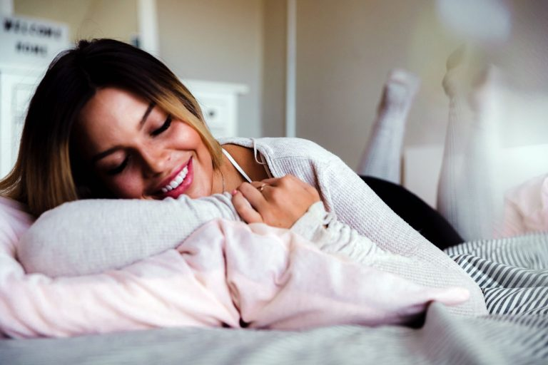 Woman resting in bed on pillow; bamboo pillow
