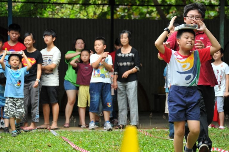 Kids playing outdoor balancing game on grass, to celebrate school birthdays without food